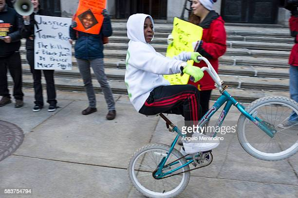 An unidentified young boy rides a bike past a group of protesters gathered outside of City Hall to protest the death of 12year old Tamir Rice in...