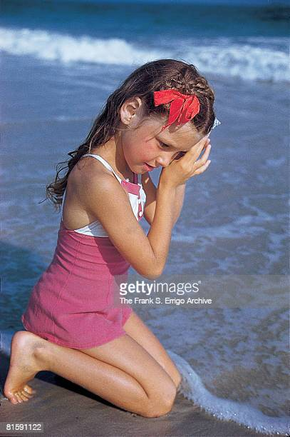 An unidentified young girl kneels down and listens to a seashell in the surf at Jones Beach Long Island New York 1942
