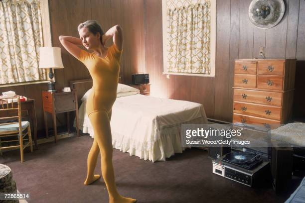 An unidentified young woman dressed in a yellow leotard and matching tights exercises in her woodpanelled room to the music from a record player on...