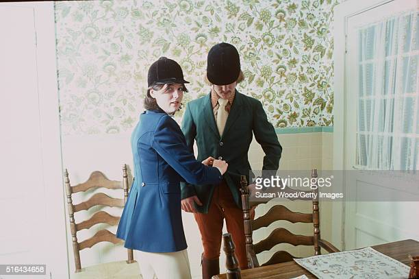 An unidentified young woman in equestrian clothing glances over her shoulder as she helps a young man button his riding coat in a Harry de Leyer's...