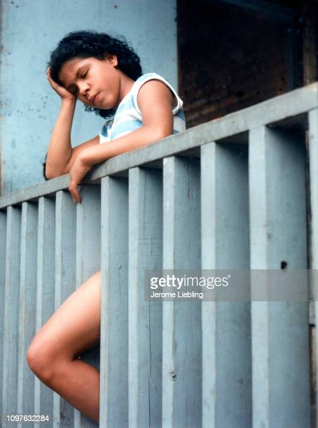 An unidentified young woman rests her head in her hand as she leans against a wooden railing behind a tenement building Holyoke Massachusetts early...