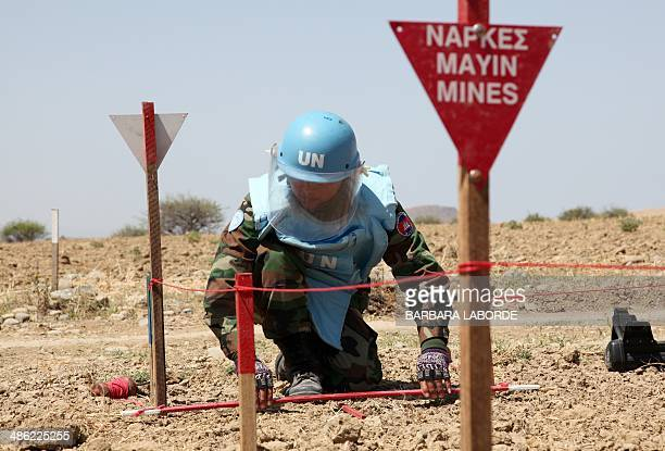 An UNIFIL's Cambodian mine expert demonstrates his work on April 23 2014 in the UNcontrolled buffer zone where demining operations are being...