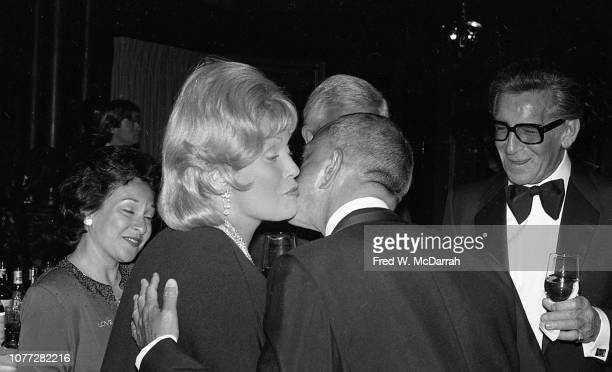 An unindentified woman shares a kissed greeting with American attorney Roy Cohn while surrounded by a group of other attendees at Cohn's birthday...