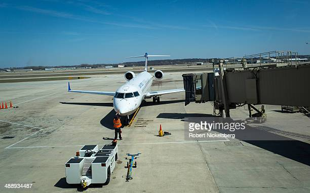 An United Express plane arrives at a docking bay April 18 2014 at the Madison Wisconsin airport United Express is the regional branch of United...