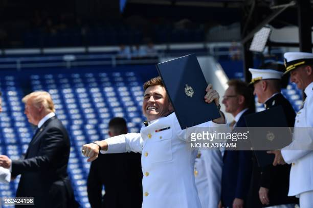 An United States Naval Academy graduate celebrates with his diploma as US President Donald Trump shakes hands during a ceremony in Annapolis Maryland...