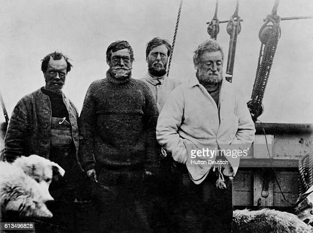 An unknown explorer Ernest Shackleton Eric Marshall and Jameson Adams together with some of the sled dogs on the Nimrod schooner