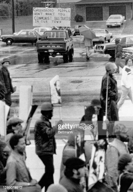 An unknown man puts up an anti-communist sign along funeral route for five communists' slain 11/3 in a gun battle with Ku Klux Klan members and...