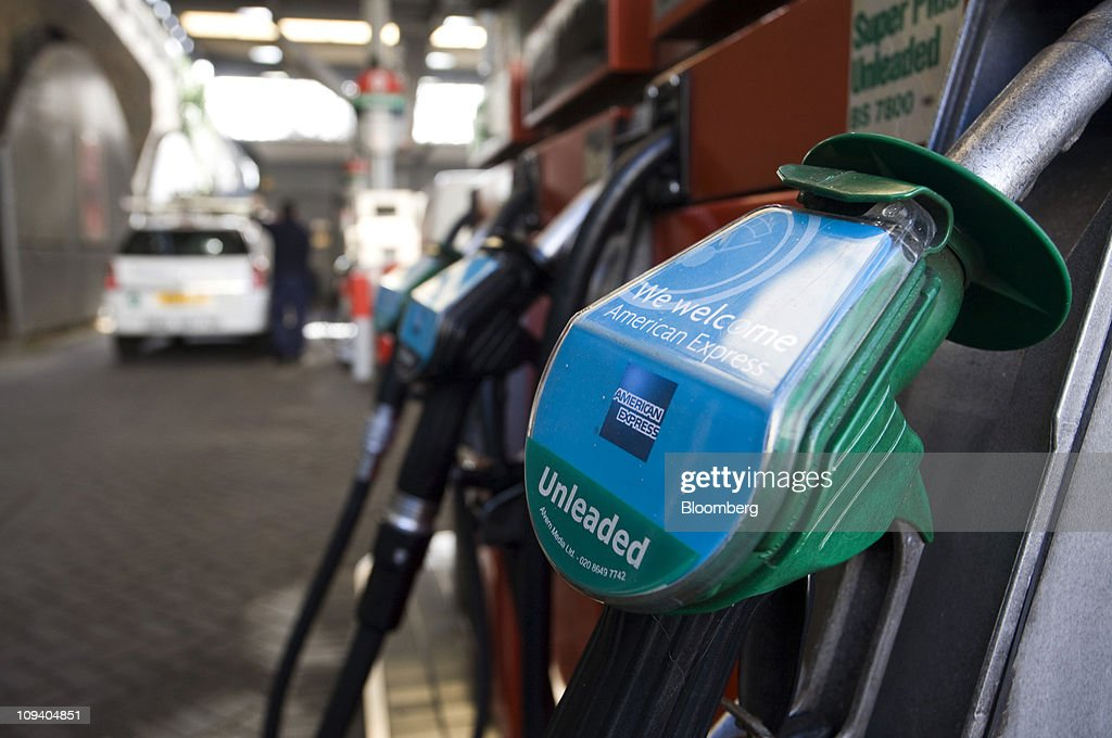 An unleaded petrol pump nozzle sits in its holder at a gas