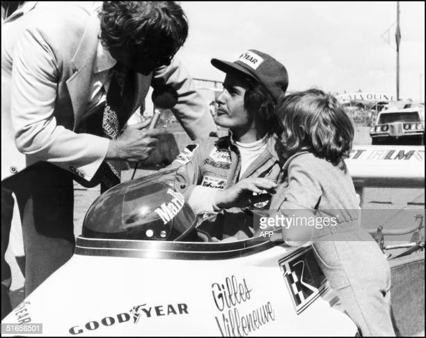 An unlocated photo taken in 1974 shows Gilles Villeneuve of Canada being interviewed in his car as his son Jacques stands by