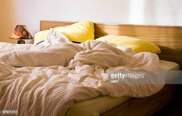An unmade bed with yellow pillows in the morning