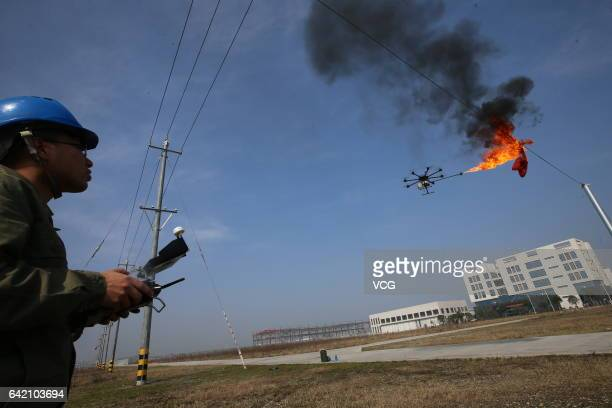 An unmanned aerial vehicle, operated by a technician, spews fire to remove a piece of plastic from the high-voltage wire on February 10, 2017 in...