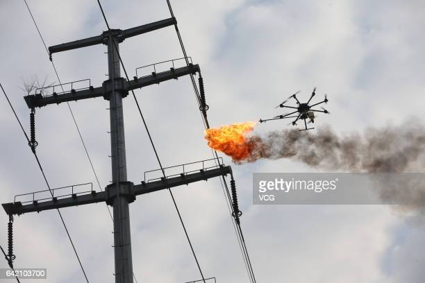 An unmanned aerial vehicle, operated by a technician, spews fire to remove a piece of plastic from the high-voltage wire on February 14, 2017 in...
