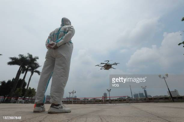 An unmanned aerial vehicle operated by an employee of SF Express transport drugs to the Liwan district under lockdown due to the recent COVID-19...