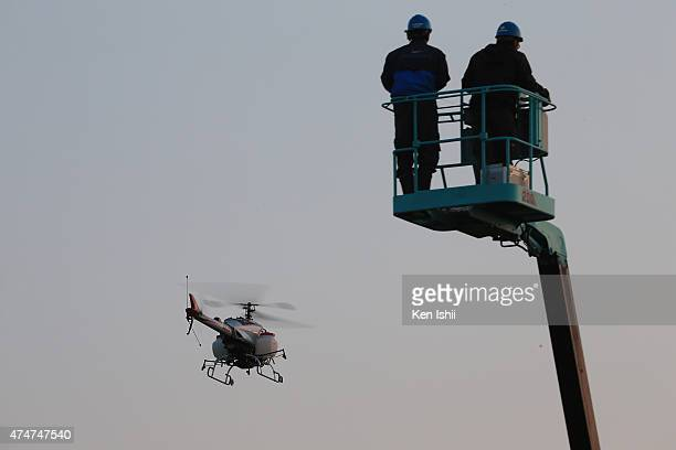 An unmanned helicopter sprays pesticides in the Mihonomatsubara or Miho Pine Grove on May 26 2015 in Shizuoka Japan An unmanned helicopter 'FAZER' of...