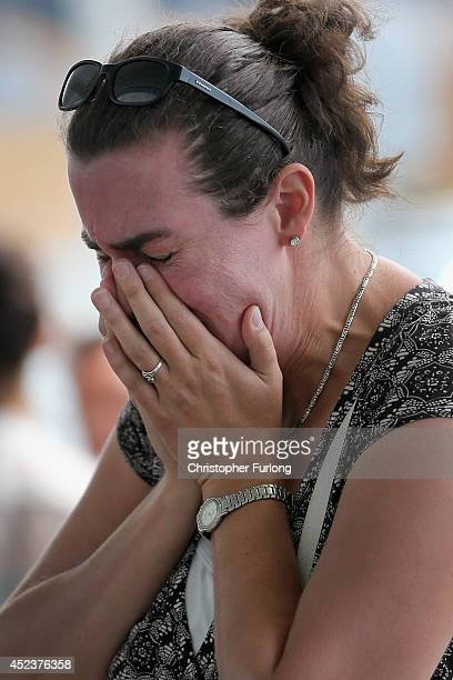 An unnamed woman weeps for a friend who was on Malaysian Airlines flight MH17 next to floral tributes adorning the entrance to Schiphol Airport in...