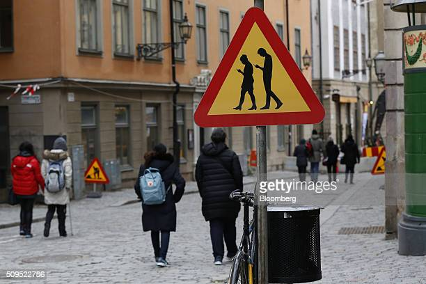 An unofficial road traffic sign warning pedestrians against endangering themselves and others by using smartphones while walking sits on a street in...