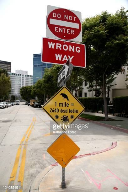 An unofficial sign reading 1 mile = 2640 dead bodies with renderings of a crow above and the coronavirus molecule below is left posted at an...