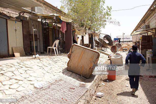 An unpaid foreign worker walks past battered seating between accomodation blocks at the Saudi Oger labor camp set up by Saudi Oger Ltd in Riyadh...