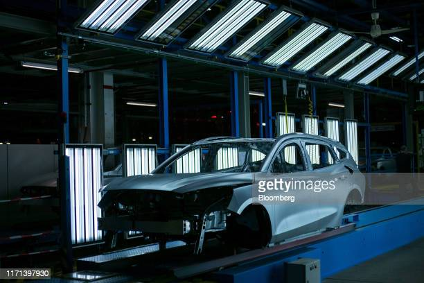 An unpainted Ford Focus automobile body stands inside a light tunnel at the Ford Motor Co. Factory in Saarlouis, Germany, on Wednesday, Sept. 25,...