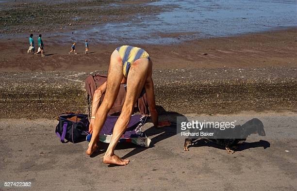 An unrecognisable bather wearing a stripy costume bends over awkwardly to adjust his towel on the promenade pavement at Minehead Devon The man's...