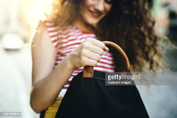an unrecognizable cheerful teenage girl standing on the street, looking for something. - borsetta da sera foto e immagini stock