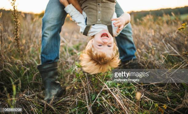 an unrecognizable father holding a toddler son upside down outdoors in autumn. - op z'n kop stockfoto's en -beelden