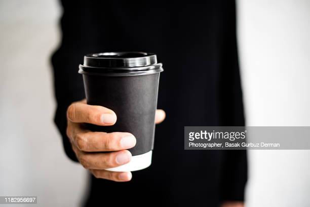 an unrecognizable man holding a disposable black coffee cup - giving stock pictures, royalty-free photos & images