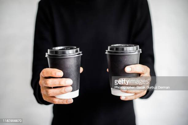 an unrecognizable man holding two disposable and black paper coffee cups with lids on - environmentalism stock pictures, royalty-free photos & images