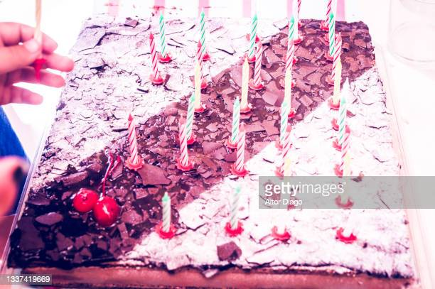 an unrecognizable person places a candle on a birthday cake with lots and lots of candles. - 100th anniversary stock pictures, royalty-free photos & images