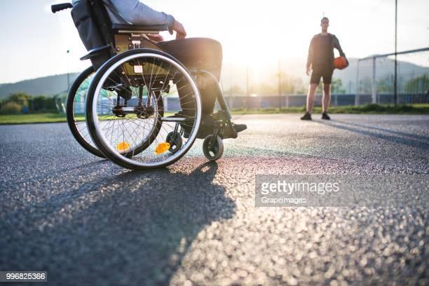 een onherkenbaar tiener in rolstoel jongen spelen basketbal kijken. - uitsluiting stockfoto's en -beelden