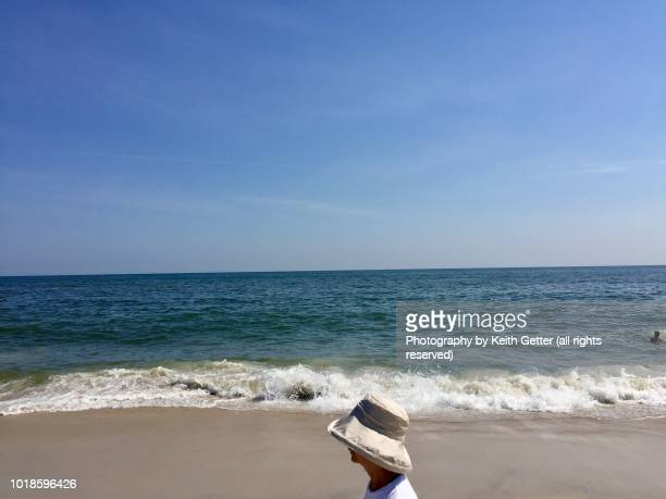 an unrecognizable woman in a sun hat on an ocean beach - wantagh stock pictures, royalty-free photos & images