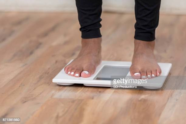 an unrecognizable woman stands on a bathroom scale - comparison stock pictures, royalty-free photos & images