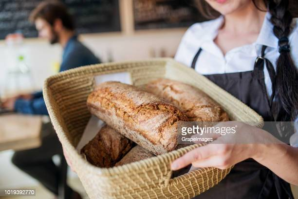an unrecognizable young female shop assistant holding a basket with bread in a zero-waste store. - bread stock pictures, royalty-free photos & images