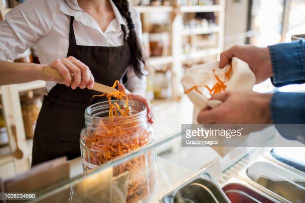 an unrecognizable young female shop assistant serving a male customer in a zero-waste store. top view. - reusable stock pictures, royalty-free photos & images