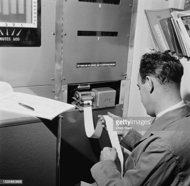 An unspecified man inspecting the ticker tape emerging from Instam, a device for obtaining ratings instantaneously via a telephone connection to...