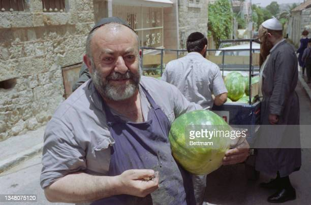 An unspecified man wearing a blue apron over a grey shirt, and a black yarmulke, carrying a melon under his left arm, as tow men stand beside a truck...