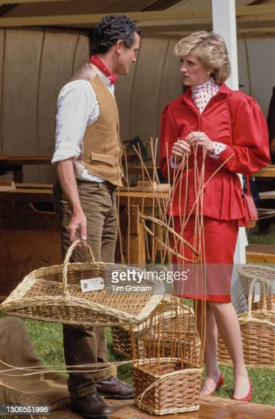 An unspecified man wearing a waistcoat with a red neckerchief and holding a wicker basket speaks to British Royal Diana, Princess Of Wales who wears...