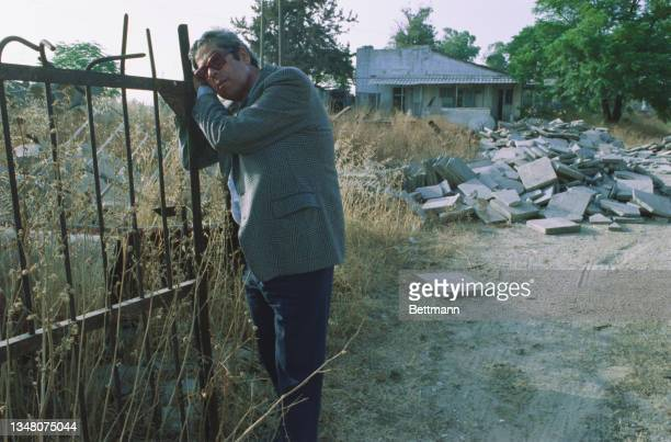 An unspecified Middle Eastern man stands by the gate of a property, with discarded paving stones in the background, an unspecified area of the West...