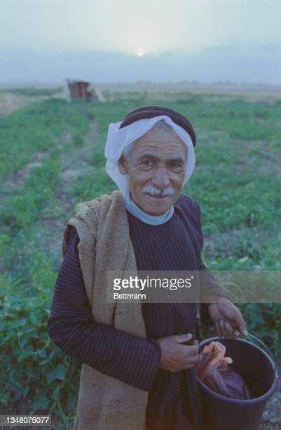 An unspecified Middle Eastern man, with a blanket over his shoulder, wearing a white keffiyeh, stands holding a bucket, an unspecified area of the...