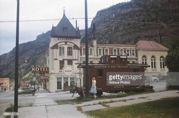 An unused train carriage marked as The Chamber of Commerce Information Point on Main Street Ouray Colorado circa 1962 The Hotel Beaumont can also be...