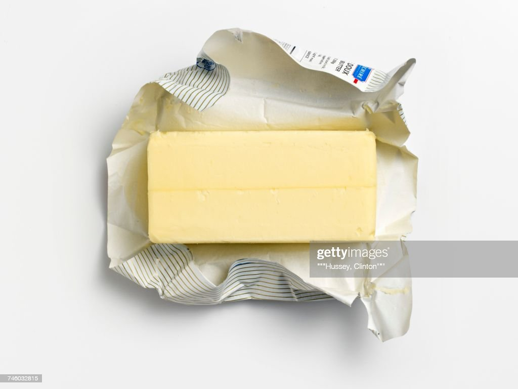 An unwrapped pat of butter on its wrapper : Stock Photo
