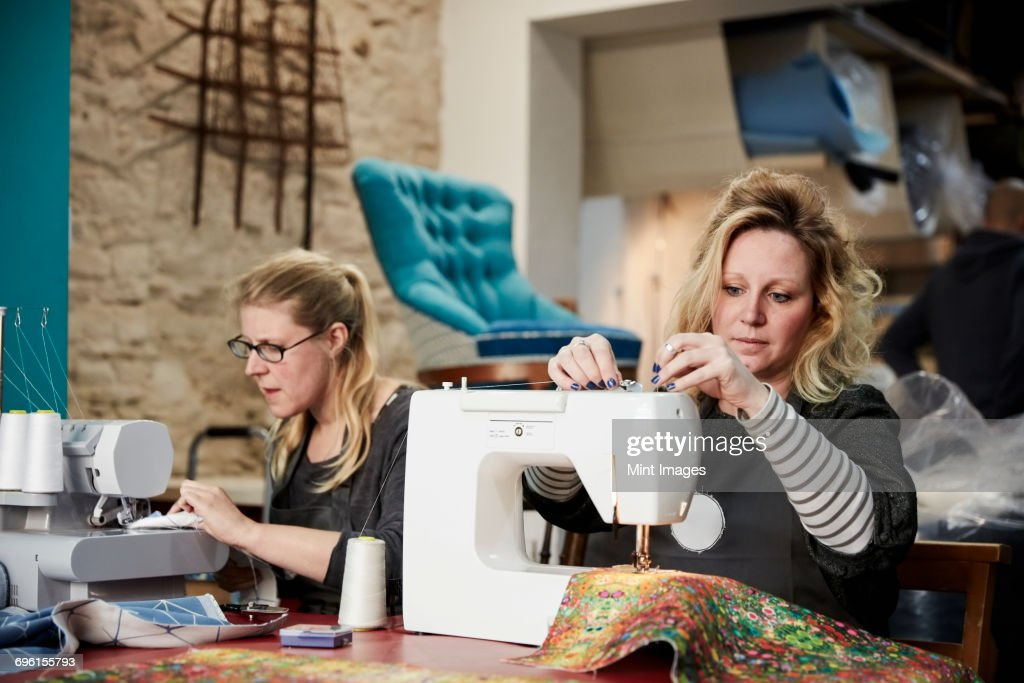 An upholstery workshop. Two women seated using sewing machines. : Stock Photo