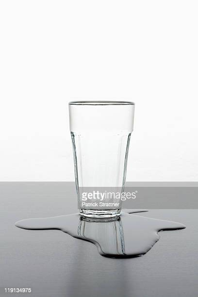 an upright glass standing in a puddle of spilled water - spilling stock photos and pictures