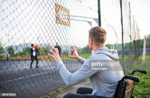 an upset teenager in wheelchair looking at boys playing basketball from behind mesh fence. - wire mesh stock pictures, royalty-free photos & images