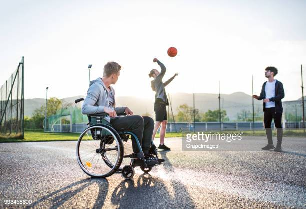 an upset teenager in wheelchair looking at boys playing basketball outdoors. - exclusion stock pictures, royalty-free photos & images