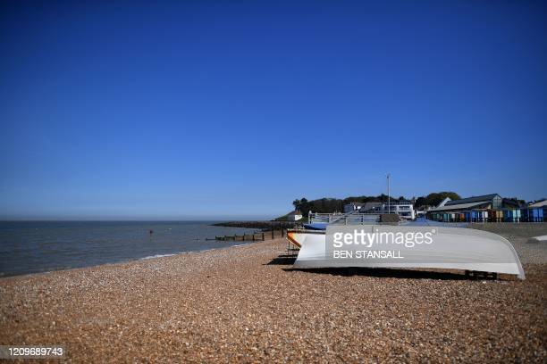 An upturned boat is pictured on the empty beach at Whitstable south east England on April 11 as life in Britain continues over the Easter break...