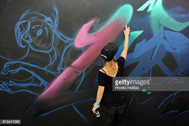 An urban artist sprays graffiti during the International Festival of Graffiti at downtown of Mexico City on October 8 2016 / AFP / PEDRO PARDO