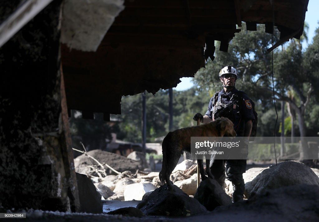 An urban search and rescue team member and his dog search a home that was destroyed by a mudslide on January 11, 2018 in Montecito, California. 17 people have died and hundreds hundreds of homes have been destroyed or damaged after massive mudslides crashed through Montecito, California early Tuesday morning.