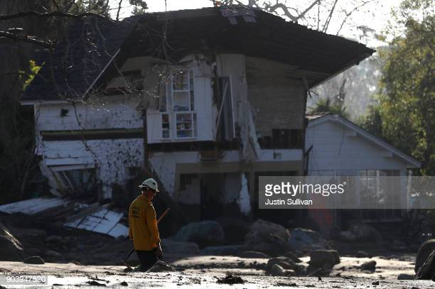An urban search and rescue team member walks by a home that was destroyed by a mudslide on January 11 2018 in Montecito California 17 people have...
