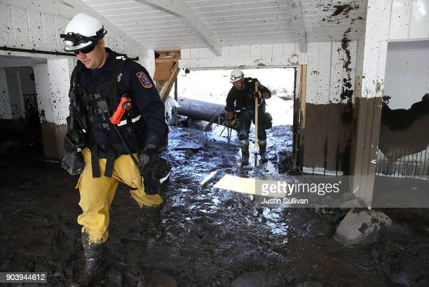 An urban search and rescue team searches a home that was destroyed by a mudslide on January 11 2018 in Montecito California 17 people have died and...